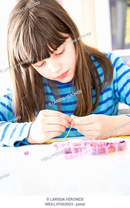 Girl stringing pearls
