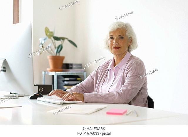 Portrait of smiling woman using computer while sitting against wall in office