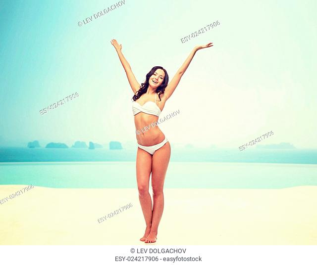 people, fashion, swimwear, summer and beach concept - happy young woman posing in white bikini swimsuit dancing with raised hands over infinity pool at beach...