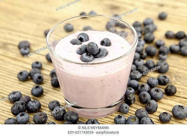Frischer leckerer Joghurt mit Heidelbeeren und Blaubeeren isolie