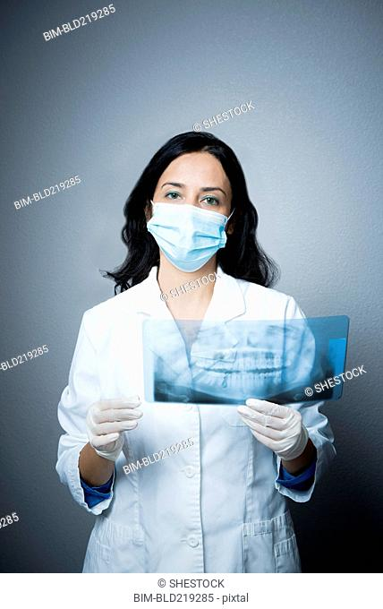 Indian dentist in face mask examining x-rays