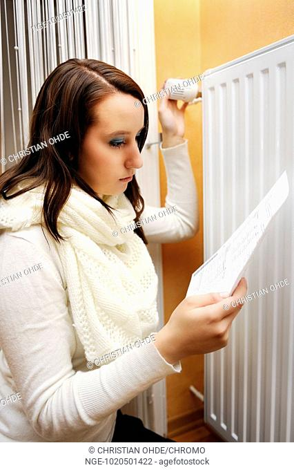 Young woman with heat billing in front of a heater, heating costs