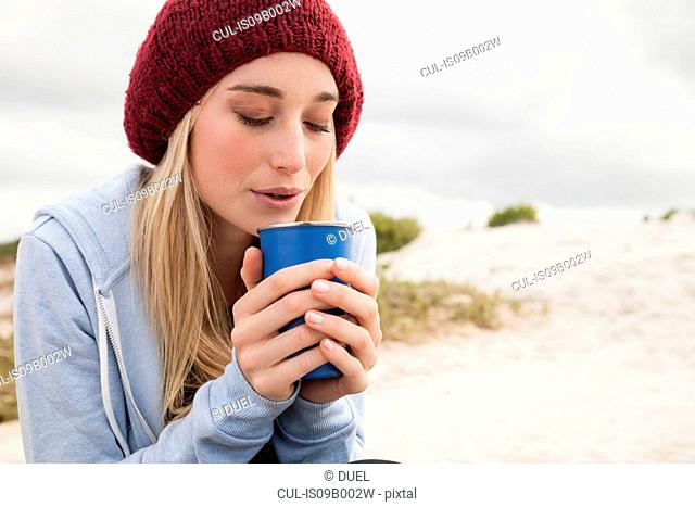 Young woman blowing into cup of coffee on cold day
