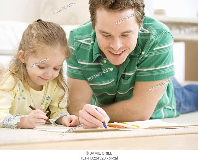 Father and daughter coloring on floor
