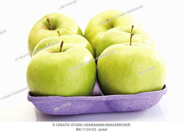 Granny Smith apples on a plastic tray