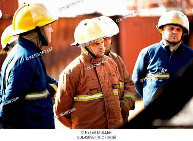 Firemen training, team of firemen listening to supervisor at training facility
