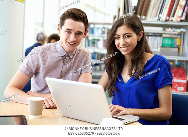 Two University Students Working In Library Using Laptop