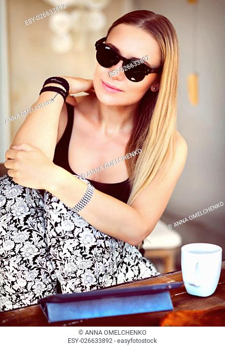 Beautiful young woman drinking coffee, enjoying nice peaceful morning at the outdoors cafe, modern life of young people