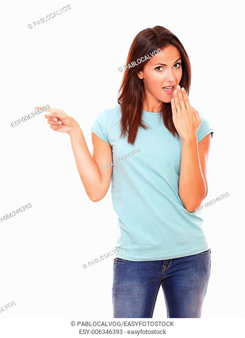 Portrait of surprised adult lady on blue t-shirt pointing to her right while looking at you on isolated white background - copyspace