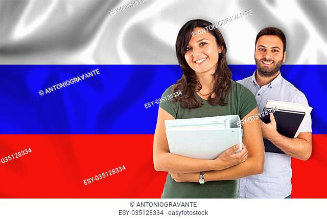 Couple of young students with books over russian flag