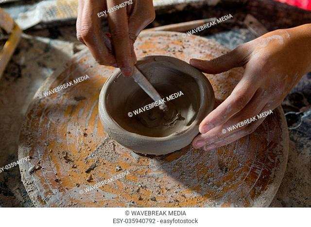 Hands of female potter molding a bowl with hand tool