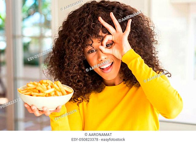 African american woman holding a plate with potato chips at home with happy face smiling doing ok sign with hand on eye looking through fingers