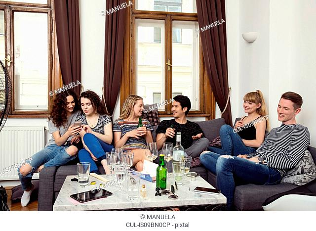 Group of male and female adult friends sitting on sofa chatting and drinking