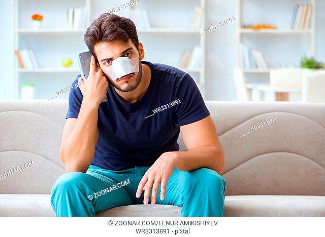 Young man recovering healing at home after plastic surgery nose job
