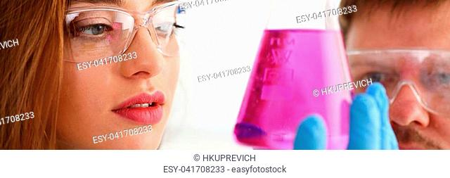 Technician hold in arms in protective gloves sample bottle with poison fluid portrait. Medical worker in uniform use reagent tube for virus infection exam or...