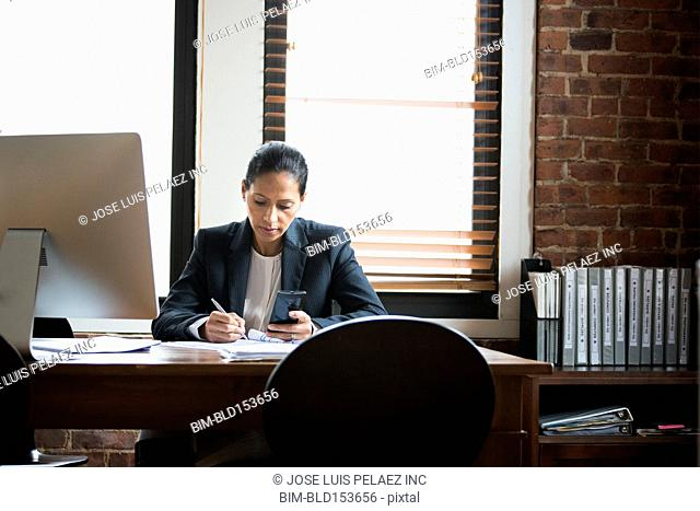 Hispanic businesswoman working at office desk