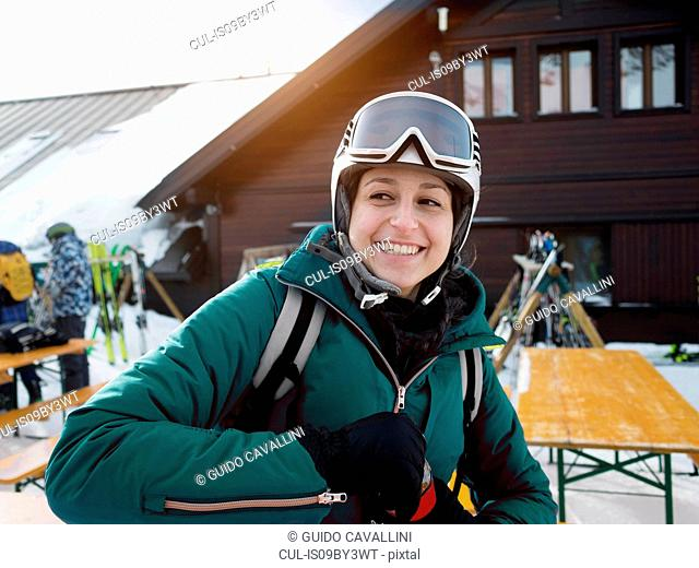 Young female skier wearing helmet and ski goggles sitting at table, Alpe Ciamporino, Piemonte, Italy