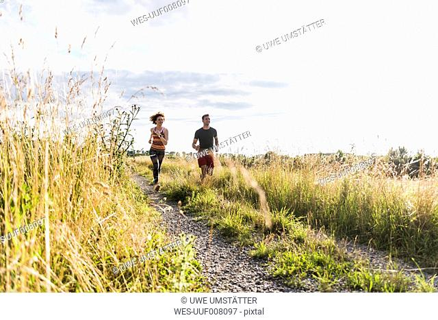 Young couple running on field path