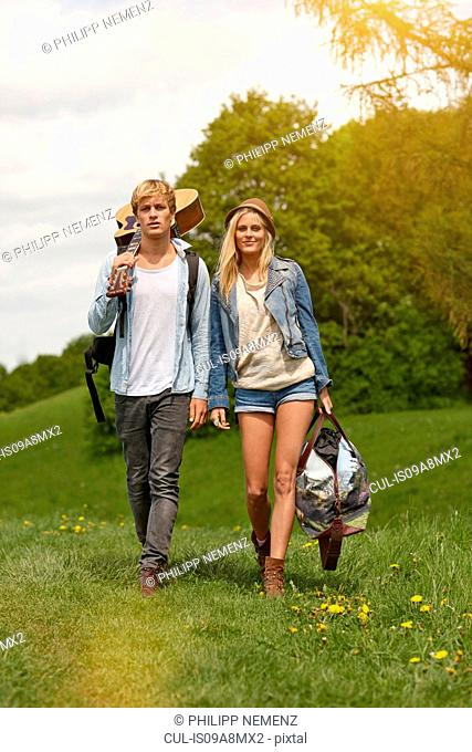 Young couple walking through field with guitar