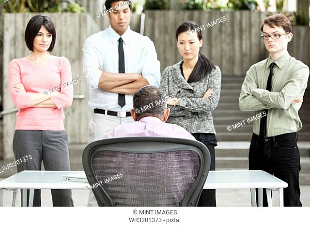 A mixed race group of business people standing in front of a person at a desk