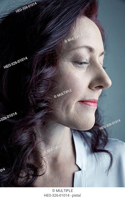 Close up portrait serious Caucasian mature woman with curly burgundy red hair looking down