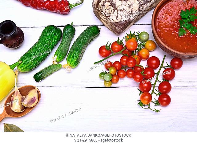 Fresh cucumber and red cherry tomatoes and a plate of cold gazpacho soup on a white table, top view, empty space in the middle