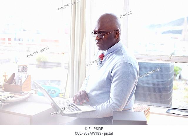 Mature man wearing eye glasses in office using laptop