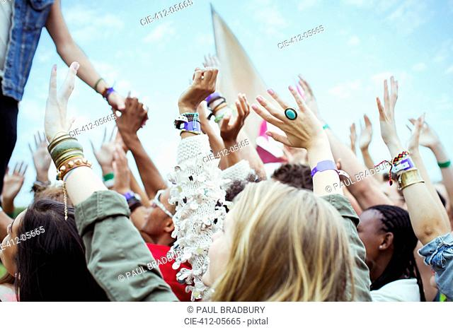 Fans reaching to shake hands with performer at music festival