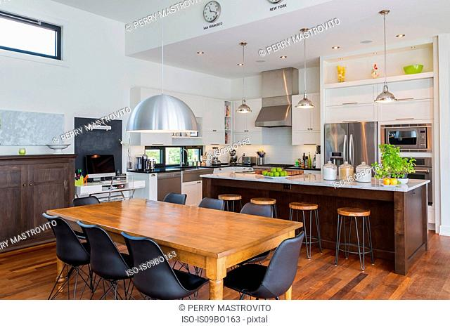 Open plan kitchen dining area with antique table, marble top kitchen island in luxurious modern cube style house interior