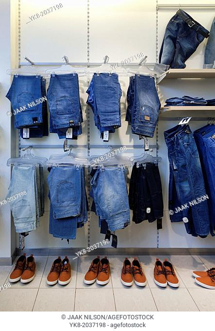 Jeans, trousers and shoes in retail shop interior. Store display with rack, shelf