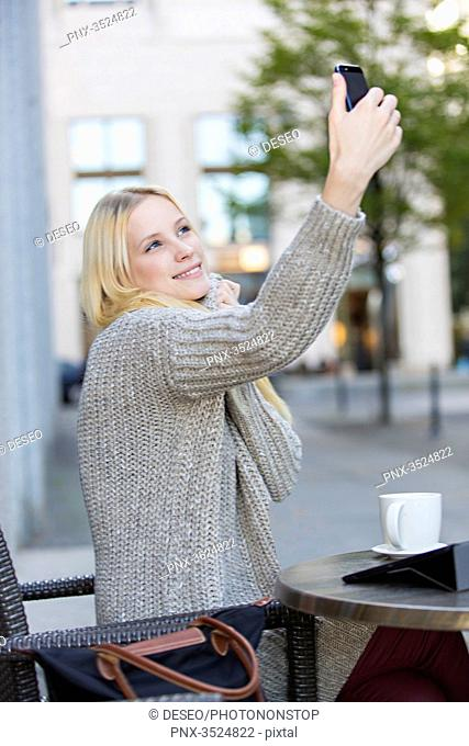 Pretty young woman doing a selfie in a Cafe in city center
