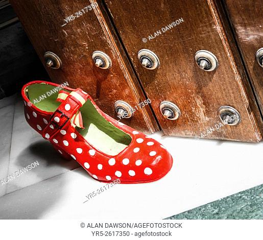 Red Polka Dot shoe used as door stop in Seville, Andalusia, Spain