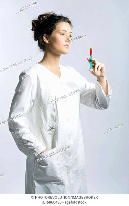 Young woman wearing a white laboratory smock looking concentrated while holding a syringe filled with red liquid in her hand