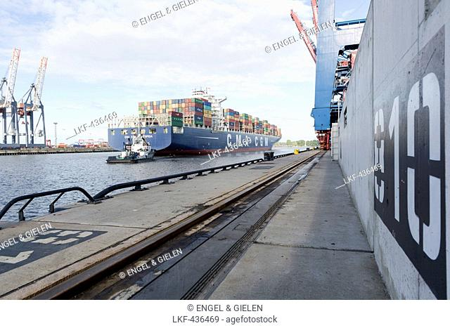Container ships being towed to the berth in the port, Burchardkai, Hamburg, Germany