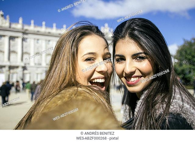 Spain, Madrid, two happy women taking a selfie in front of royal palace