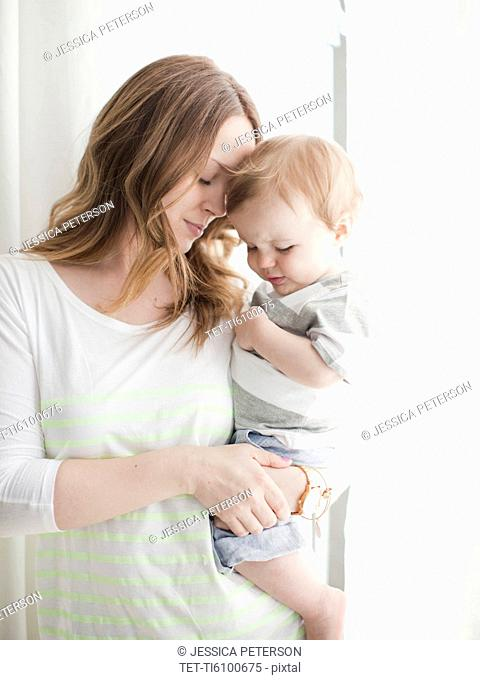 Portrait of young woman embracing baby boy 6-11 months