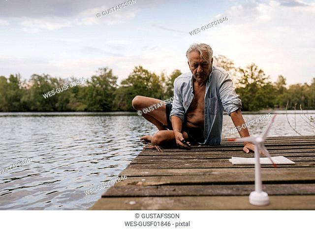 Senior man sitting on jetty at a lake with small wind turbine model