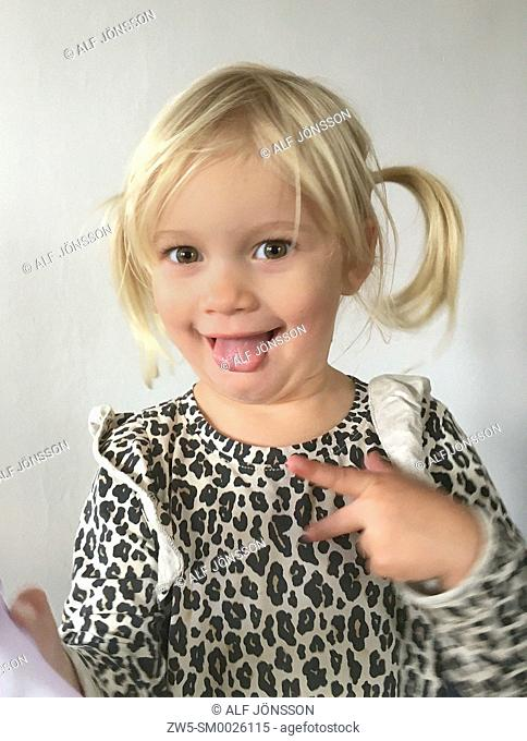 Portrait on a little blond girl who sticking out the tongue, 2 1/2 years old, in Ystad, Scania, Sweden
