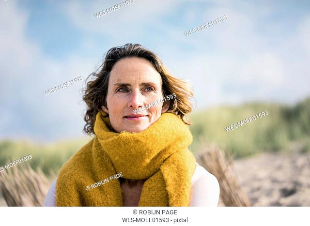 Mature woman relaxing in the dunes, enjoying the wind