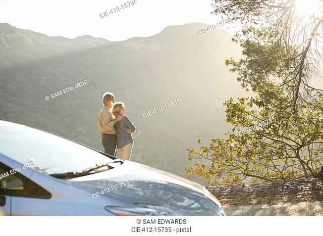 Senior couple looking at mountain view outside car