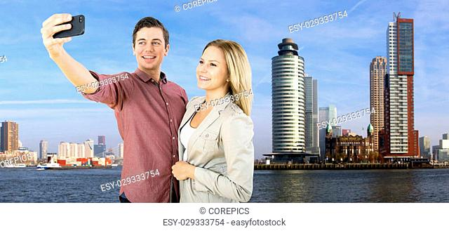 Young couple taking a selfie in front of the tall high rise buildings in Rotterdam, on the banks of the river Meuse