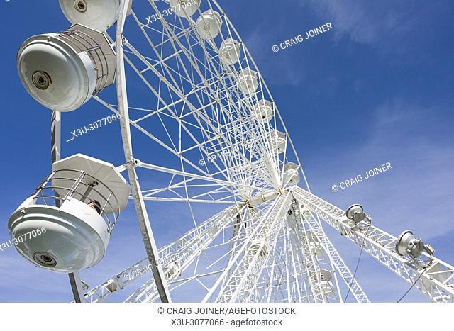 A Ferris wheel, or big wheel, at a fairground against a blue sky