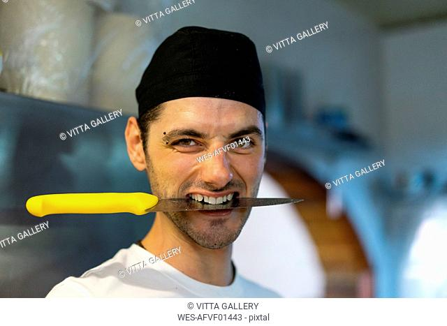 Portrait of cook in kitchen with knife between his teeth