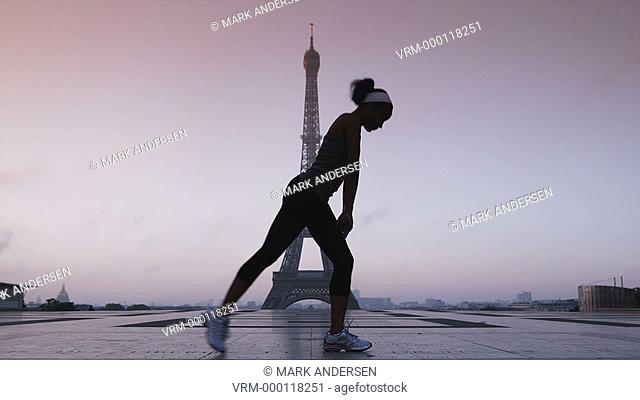 woman stretching and exercising in front of the Eiffel Tower