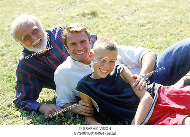 Grandfather and father lying down with young boy