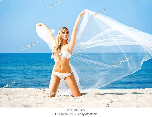 Elegant, attractive woman in alluring swimwear posing on the beach with blowing silk