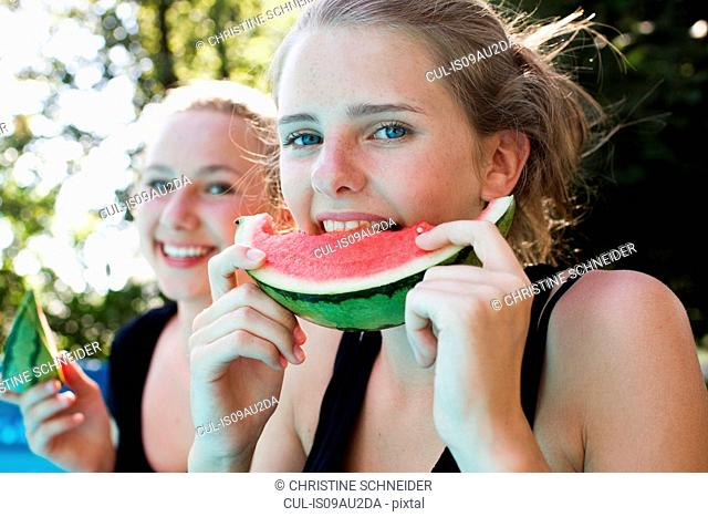 Two teenage girls eating watermelon slices in garden