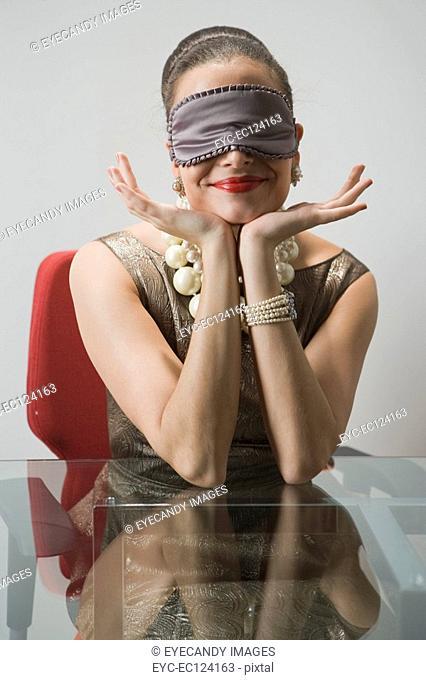 Young woman wearing eye mask, using laptop