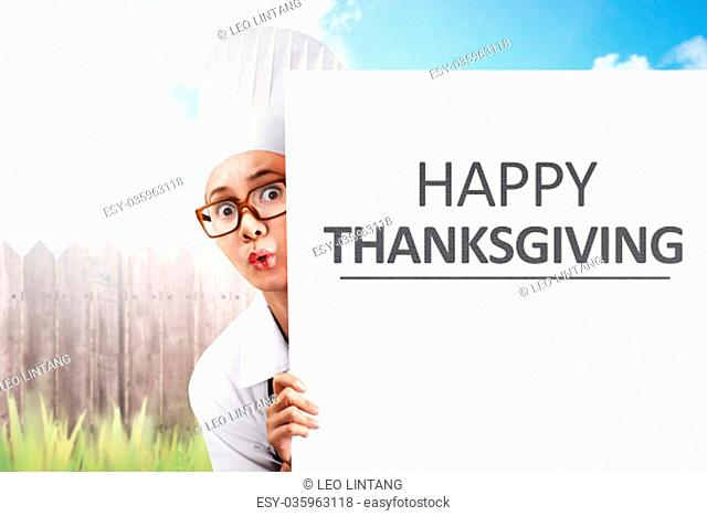Young asian woman chef holding white banner with Happy Thanksgiving message at outdoor