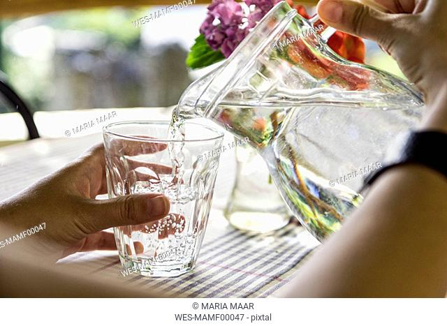Woman's hands pouring water into glass, close-up